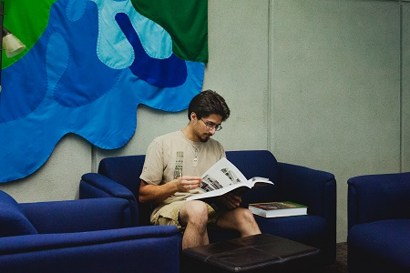 Male student reading on couch in library